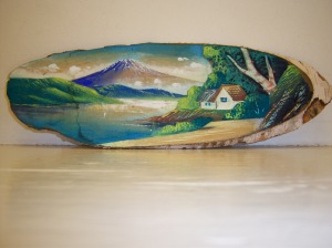 Photo of a carved wooden painting of a volcano and lake.